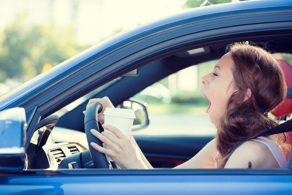 Tired woman drinking coffee & driving